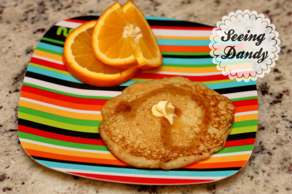 Delicious homemade pancakes recipe served withs sliced oranges on a colorful striped plate.