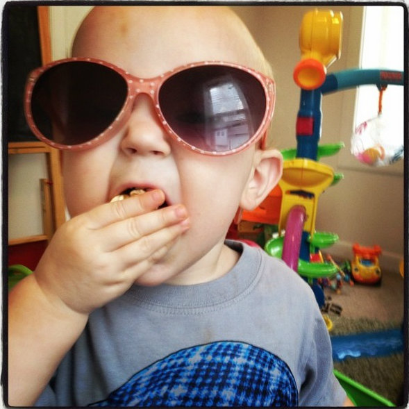 Little baby wearing polka dot sunglasses and eating kettle corn popcorn.
