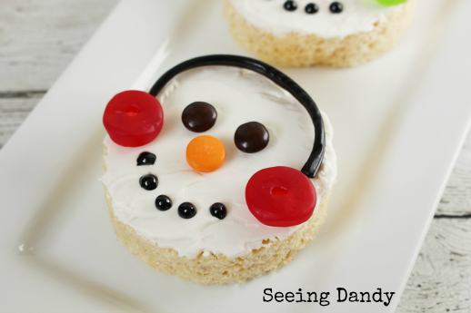 Icing covered Snowman rice krispies treats on white plate.
