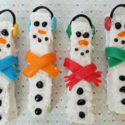 White chocolate snowmen rice krispies treats on a festive background.