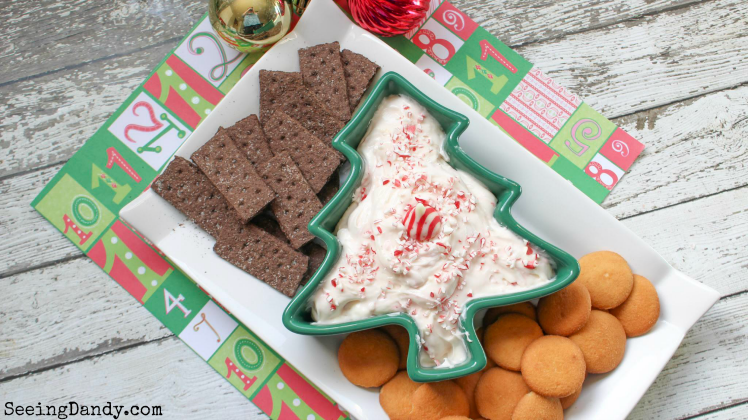 Christmas tree bowl on holiday scrapbook paper and farmhouse table with candy cane dip appetizer.