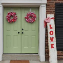 Valentine rag wreaths with love porch sign and green front door.