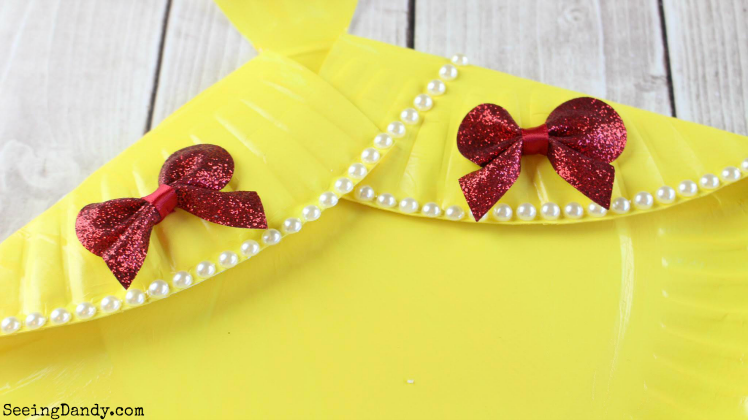 Adding red bows and pearl beads to DIY Belle dress.