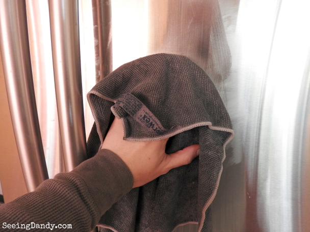 Cleaning stainless steel with a Norwex EnviroCloth.