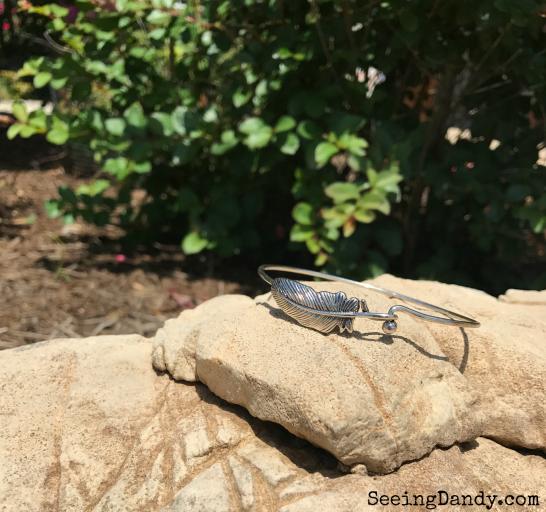 Silver feather bracelet on a rock.
