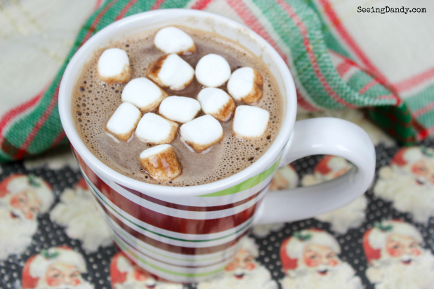Nutella hot chocolate with mini marshmallows for a Christmas party in a candy cane mug.