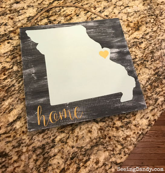 Wooden sign with Missouri outline and heart sitting on a granite countertop.