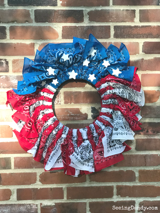 Red, white and blue 4th of July wreath hanging on a brick wall.