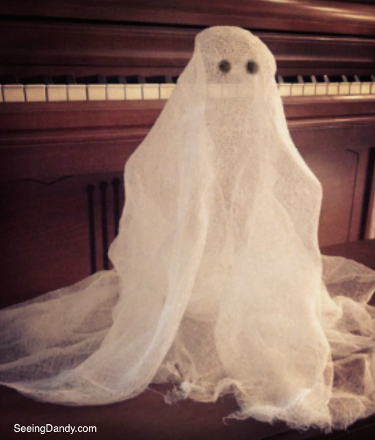 Haunting cheesecloth ghost standing up on piano bench.