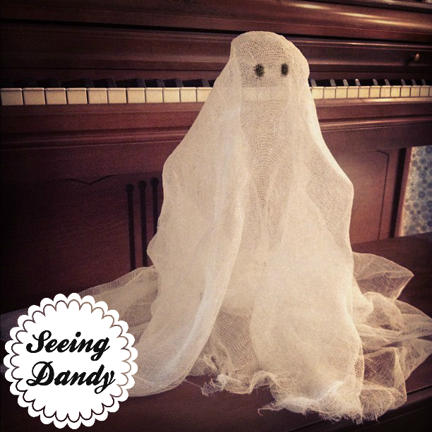 A cheesecloth ghost sitting on a piano bench in front of a piano. Simple Halloween idea.