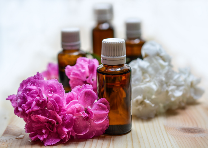 Essential oil in vials with pink and white flowers.