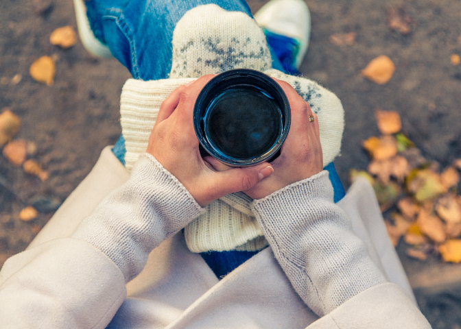 Woman wearing sweater and drinking hot chocolate with snowflake gloves.