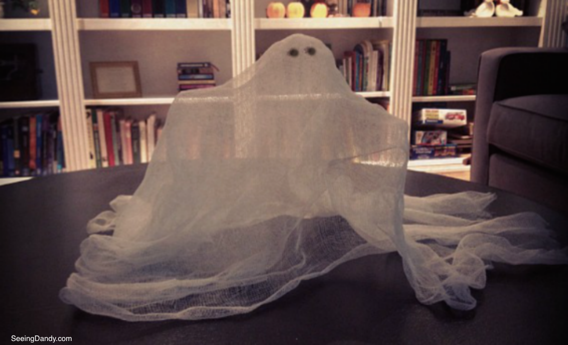 Cheesecloth ghost Halloween decor with IKEA hack bookcases.
