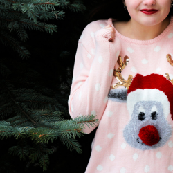 Gray reindeer ugly Christmas sweaters with pink polka dots. In front of a fir tree.