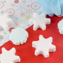 Snowflake peppermint shower steamers on festive paper with blue body wash pouf.