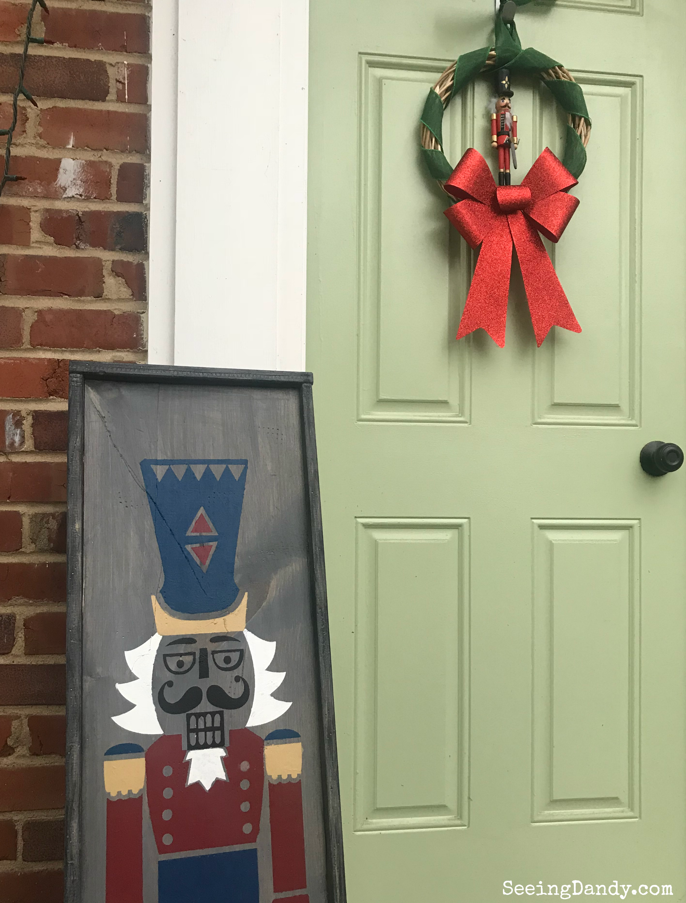 Each to make Nutcracker porch sign. Mint green front door. Brick house. Nutcracker wreath. Christmas lights.