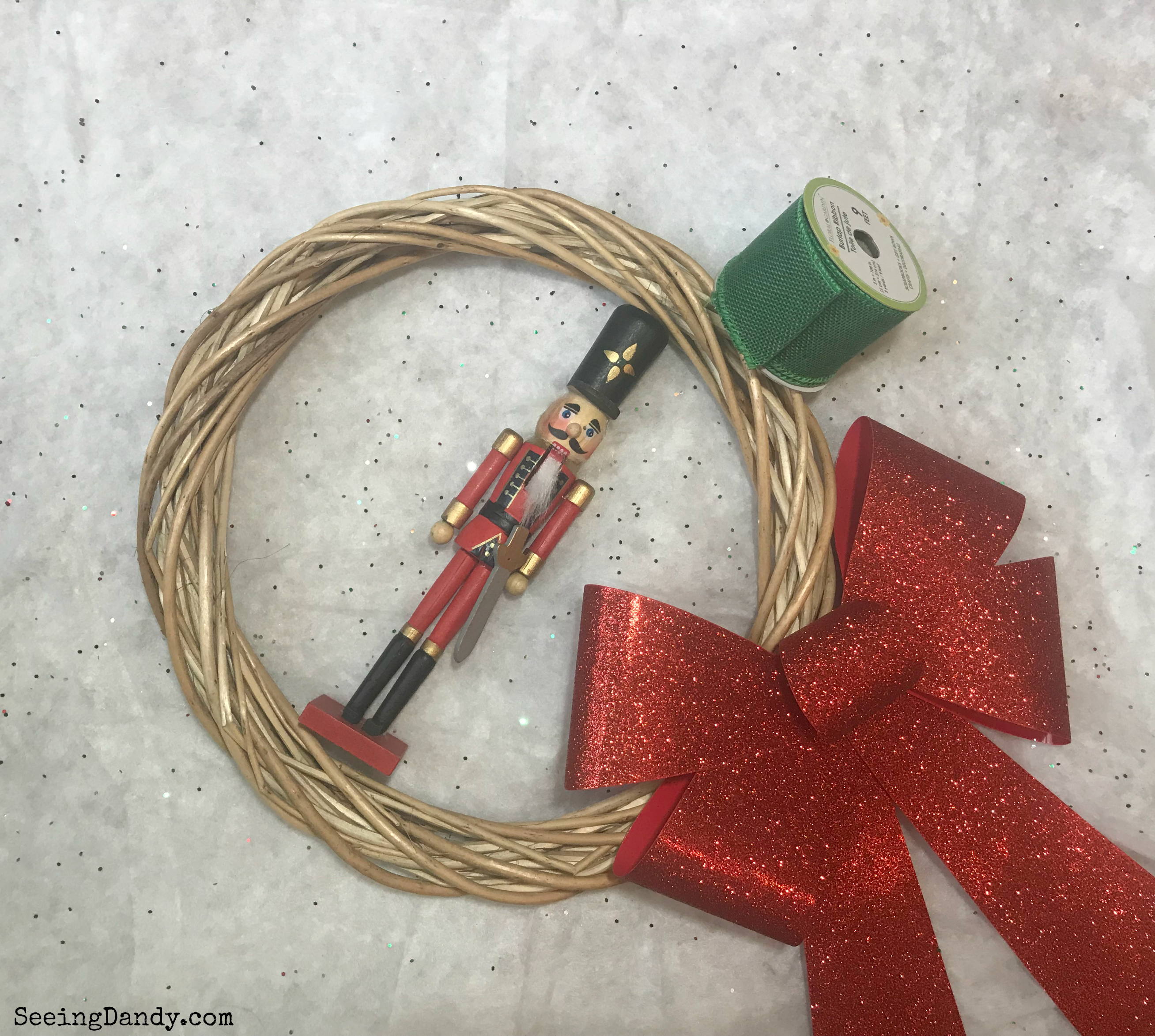 Supplies to make a DIY Nutcracker Christmas wreath. Large red ribbon, willow wreath, and green burlap ribbon.
