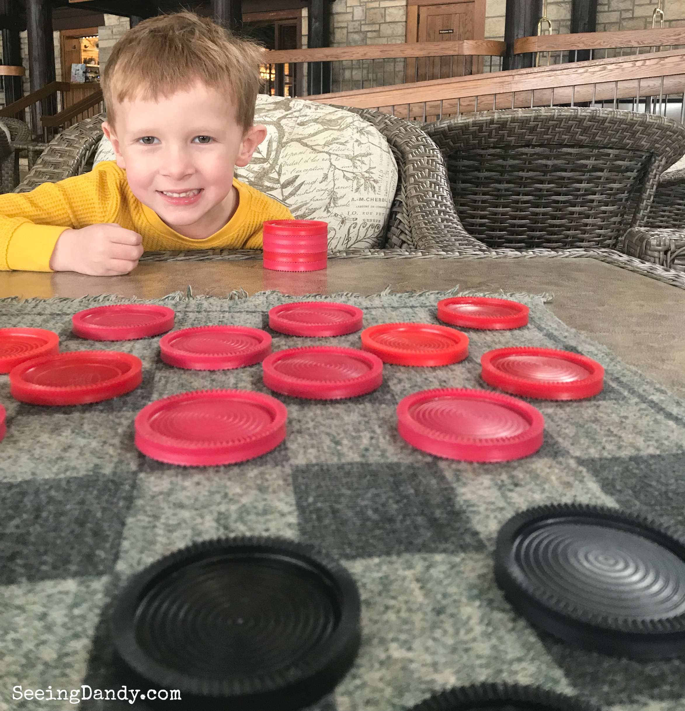 Boy playing giant checkers with fabric checker board at Pere Marquette Lodge in Grafton, IL.