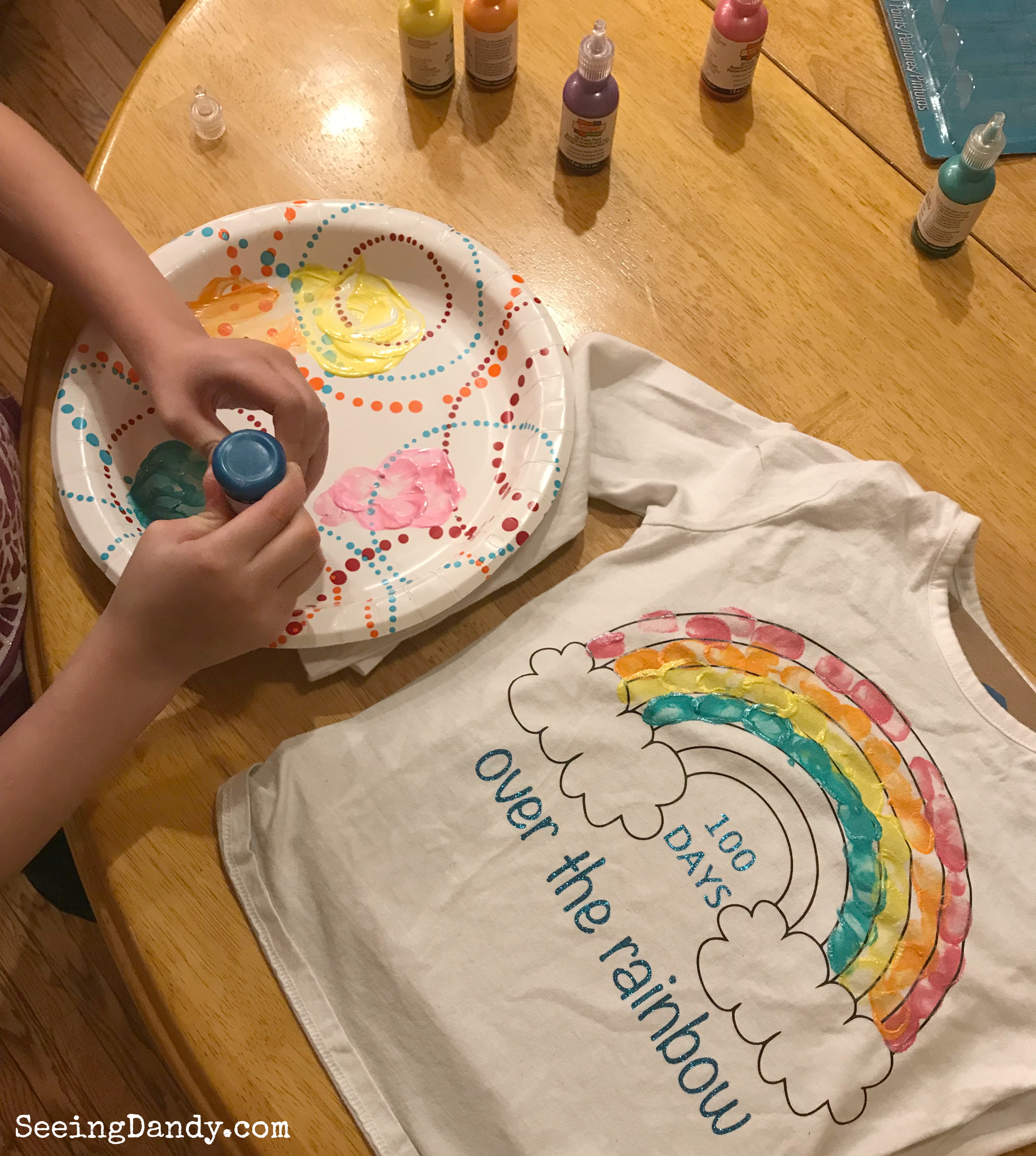 Painting 100th Day of School rainbow shirt with fingerprints.
