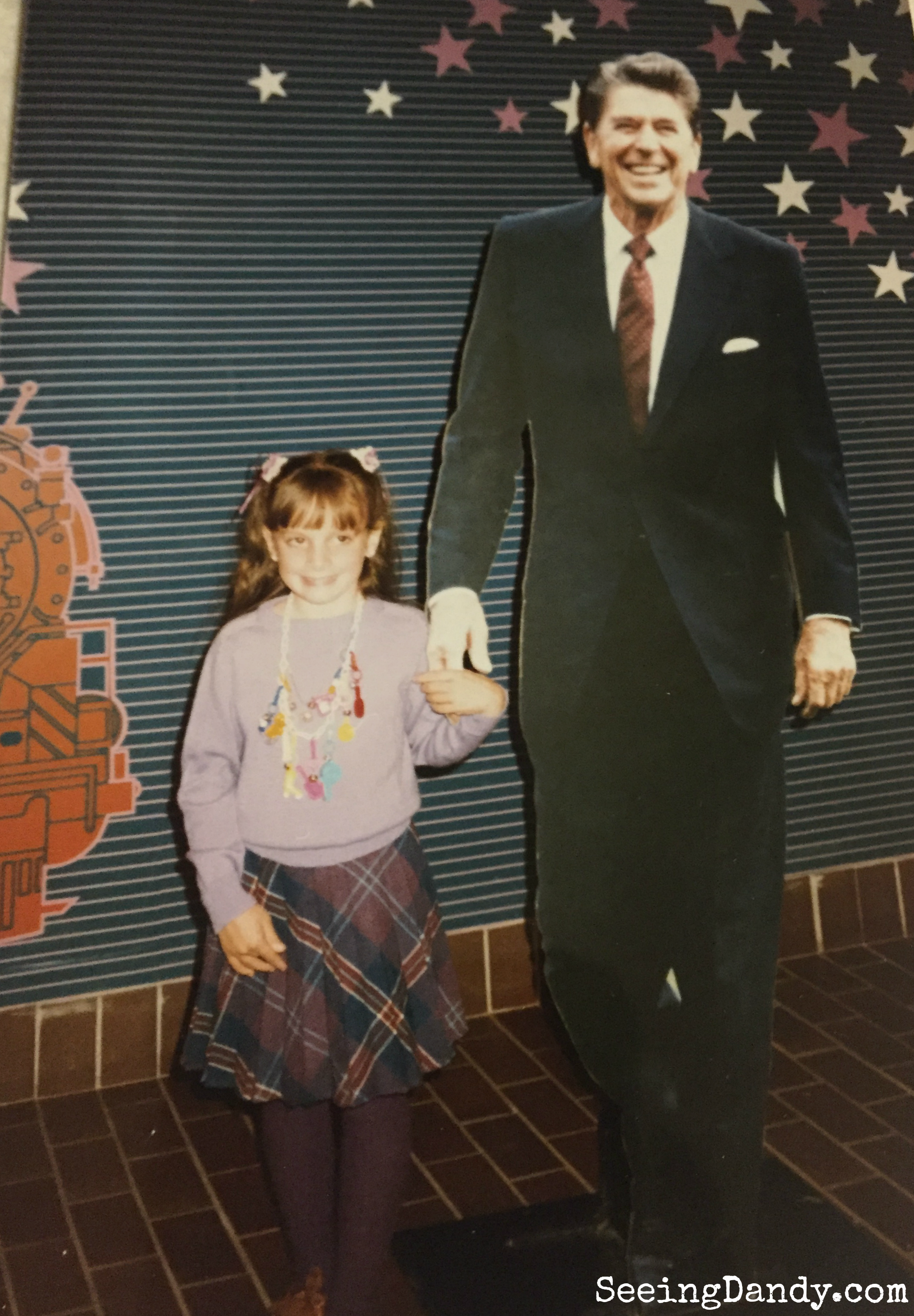 St. Louis Union Station. Girl standing with President Ronald Reagan while wearing a plastic charm necklace from the 80's.