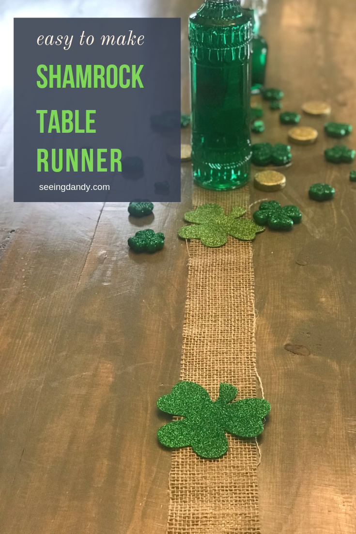 Easy to make DIY burlap shamrock table runner with green glass bottles and coins on a farmhouse table.