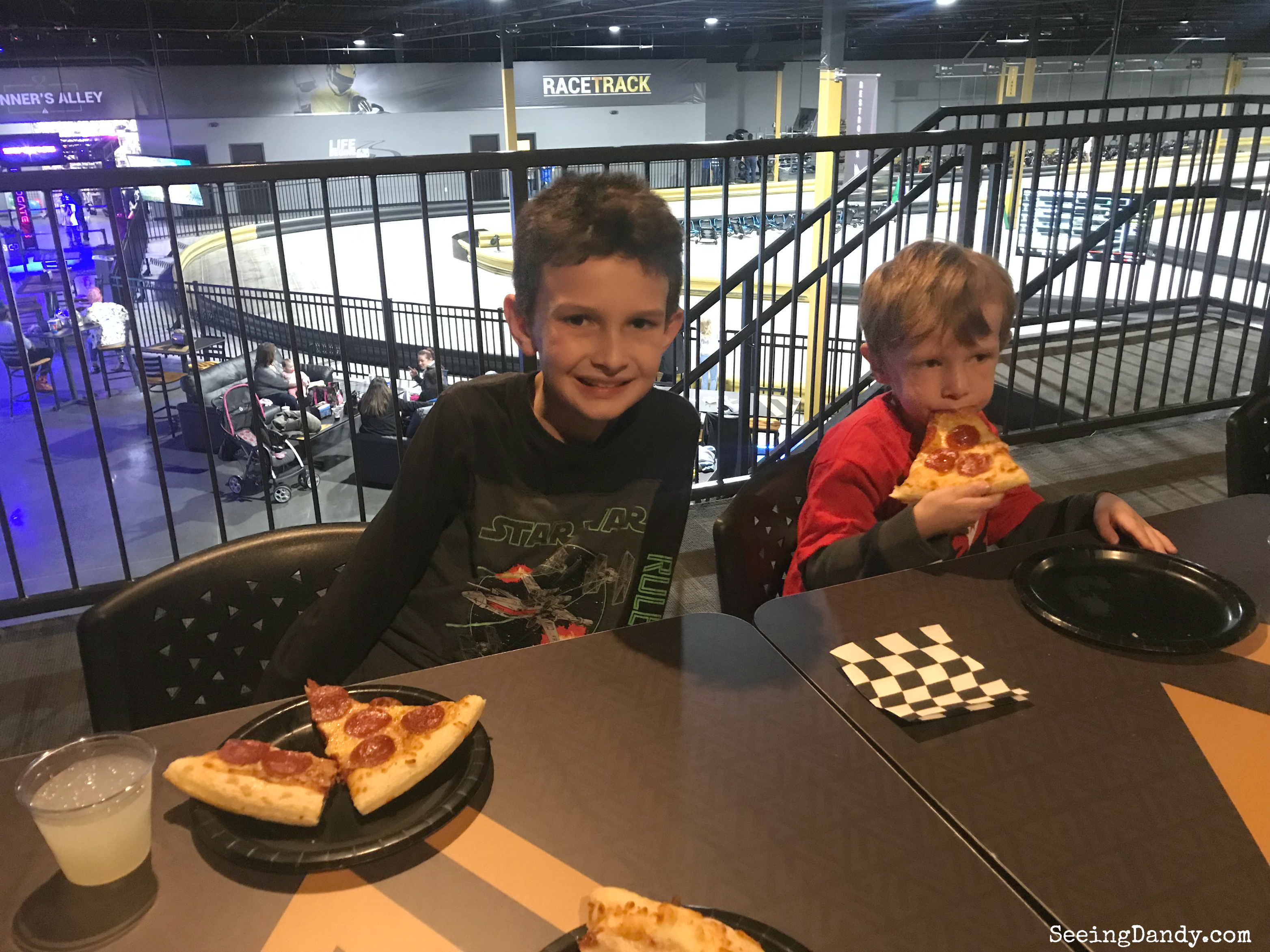Kids eating pizza and drinking lemonade with checkerboard napkins.