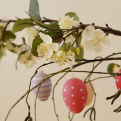 Bright color Easter eggs hung on a flowering tree branch for spring decoration.