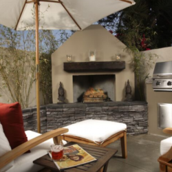 Patio fireplace with built in grill, teak chairs and umbrella.