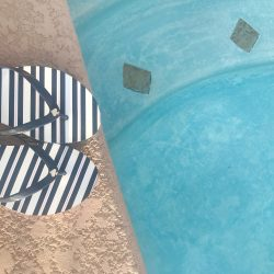 Swimming pool and stripe flip flops in blue and white.