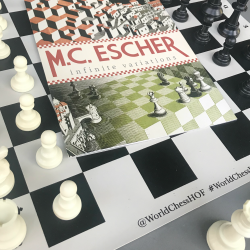 MC Escher Infinite Variations exhibit pamphlet on chess board.