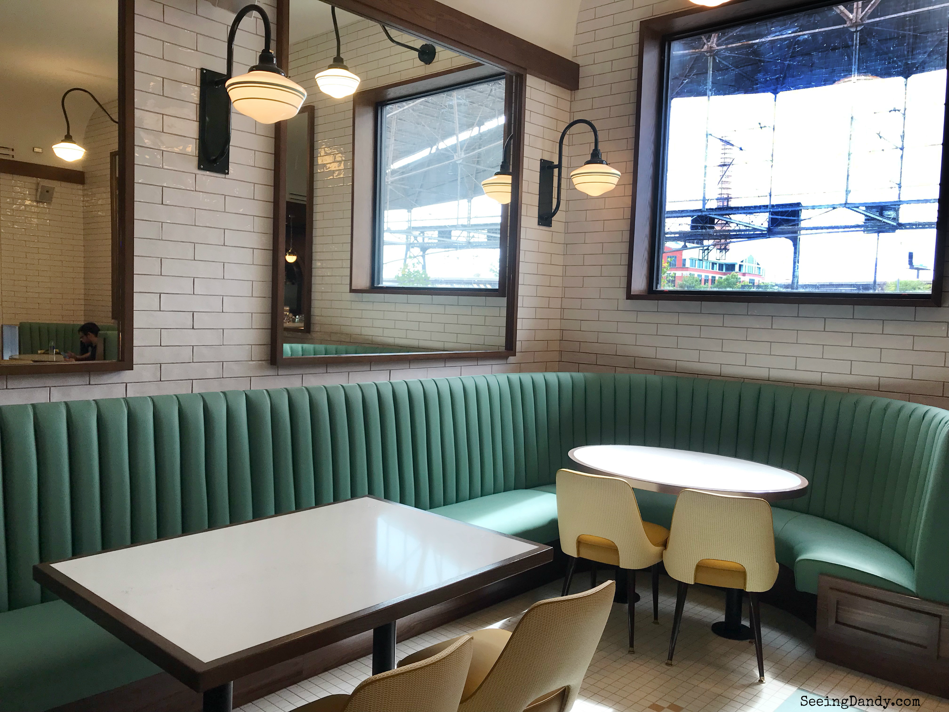 Vintage eating area with mint green booths and retro white subway tile.