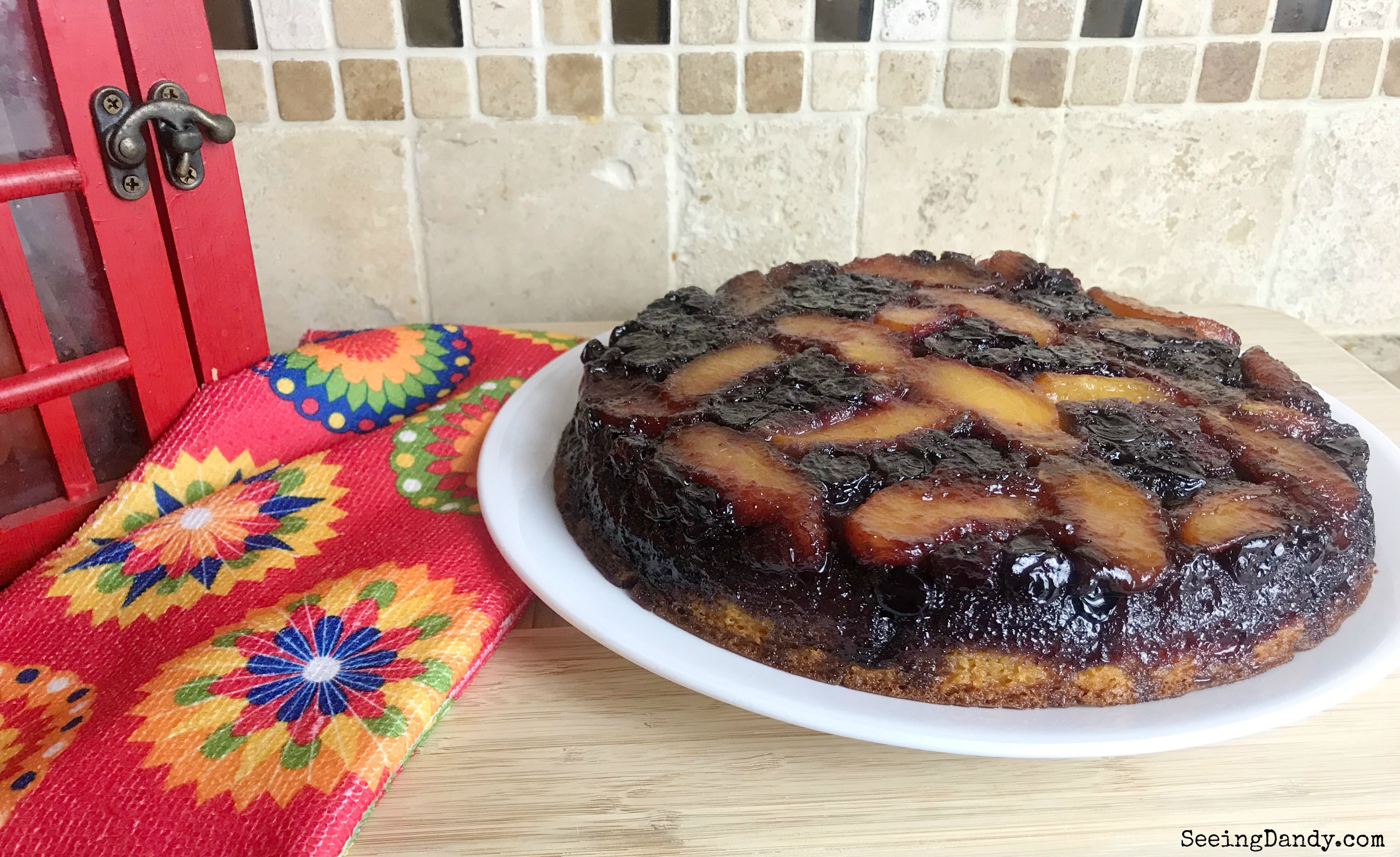 Peach blueberry upside down cake in a modern kitchen with glass tile backsplash.