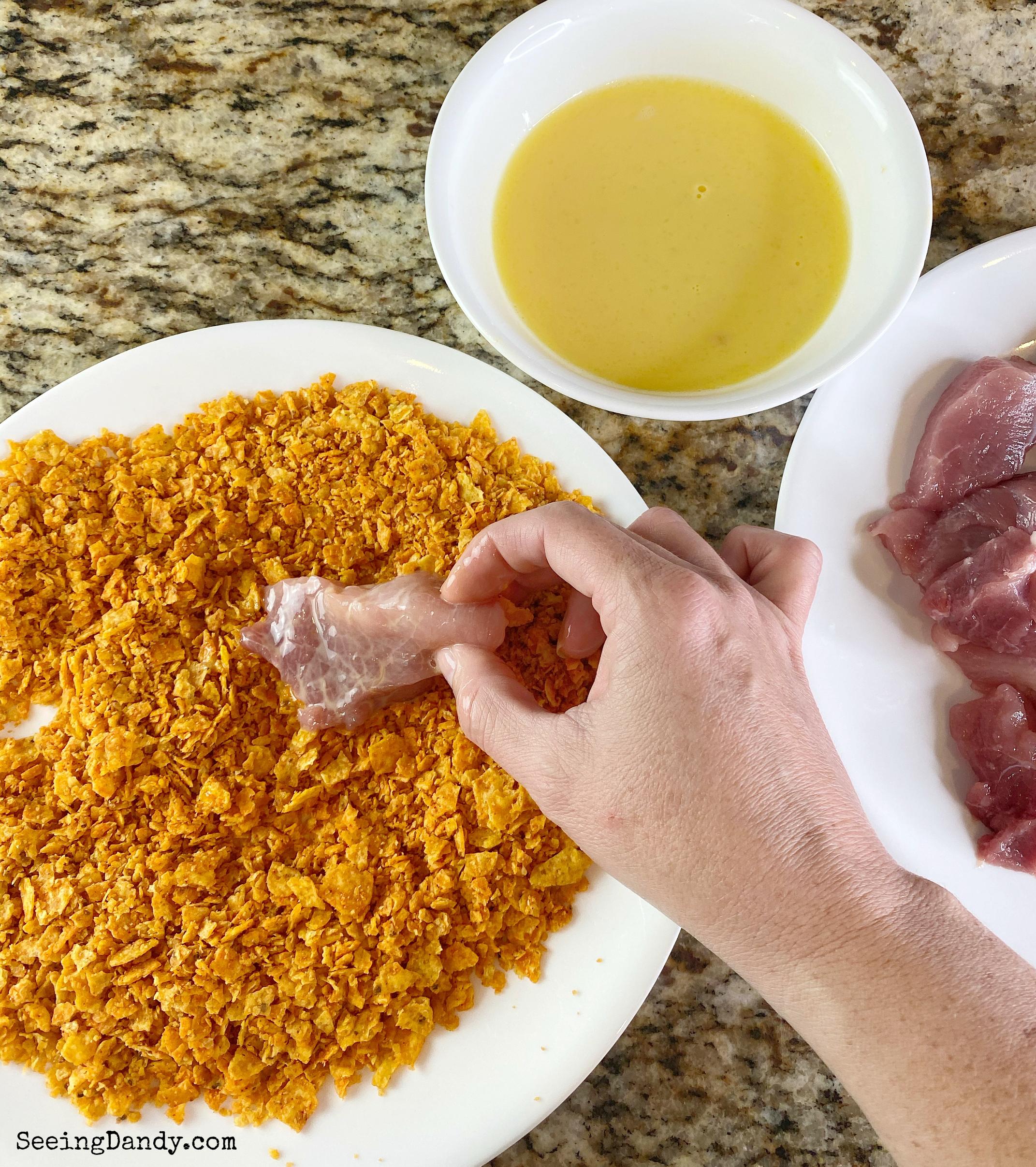 Rolling pork sirloin strips into crushed Doritos.
