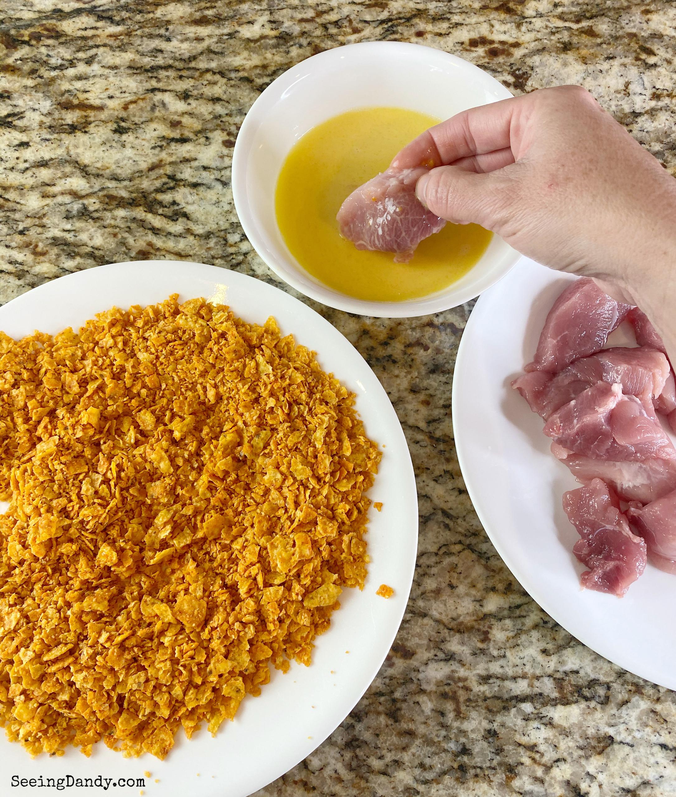 Dipping pork sirloin strips into egg.