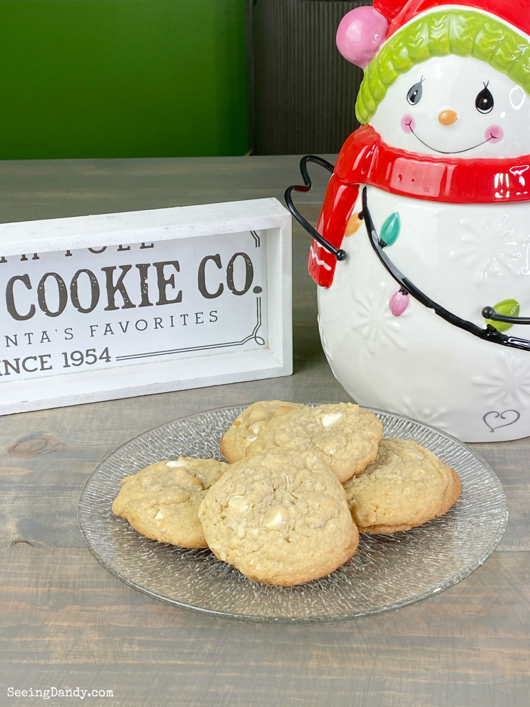 Cookies on farmhouse table with Precious Moments snowman cookie jar and Santa's cookie company sign.