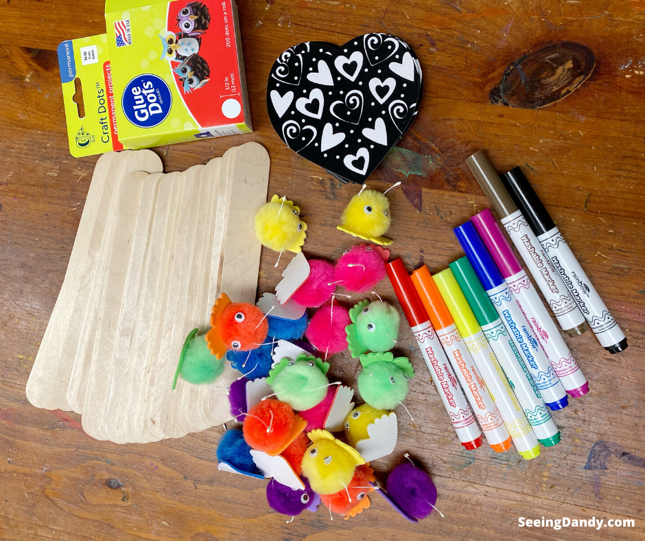 Supplies for making book buddies, jumbo popsicle sticks, glue dots, felt coloring heart, pom pom creatures, washable markers