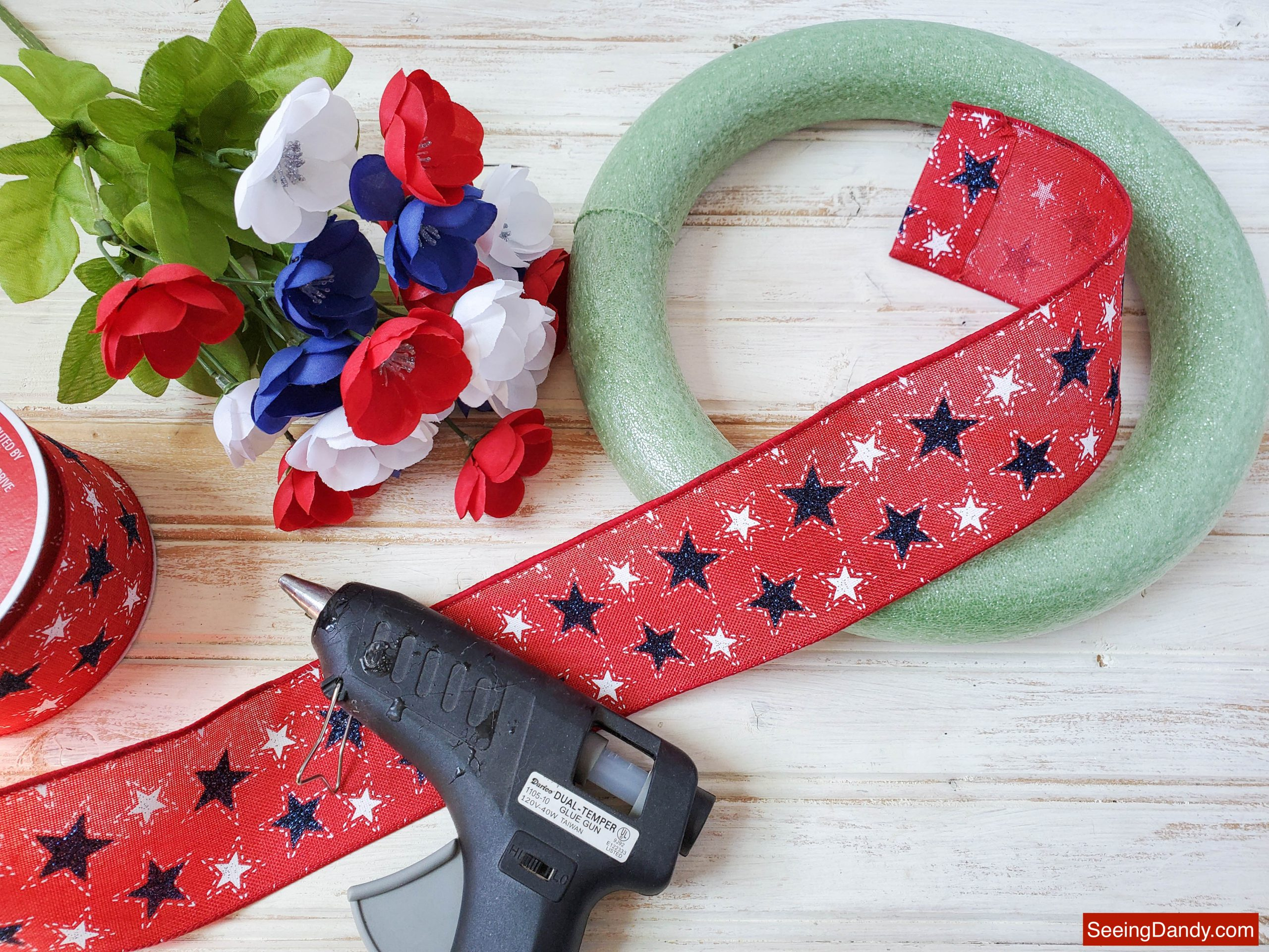 diy wreath supplies, red white blue star ribbon, patriotic poppy flowers, glue gun, green foam wreath