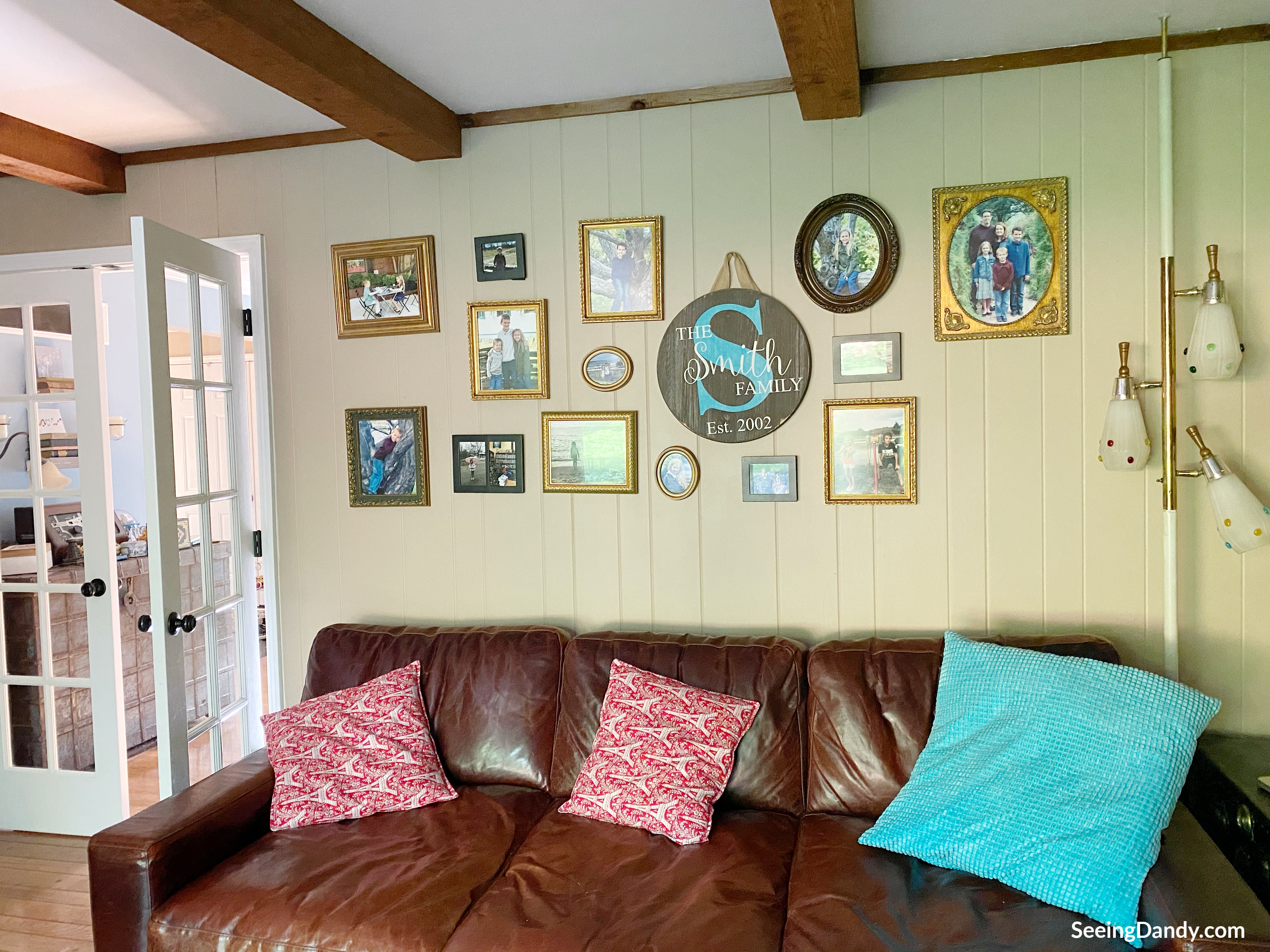 vintage picture frames, gallery photo wall, diy, family pictures, red eiffel tower pillows, farmhouse style, vintage pole lamp, ceiling wood beams, painted wood paneled wall