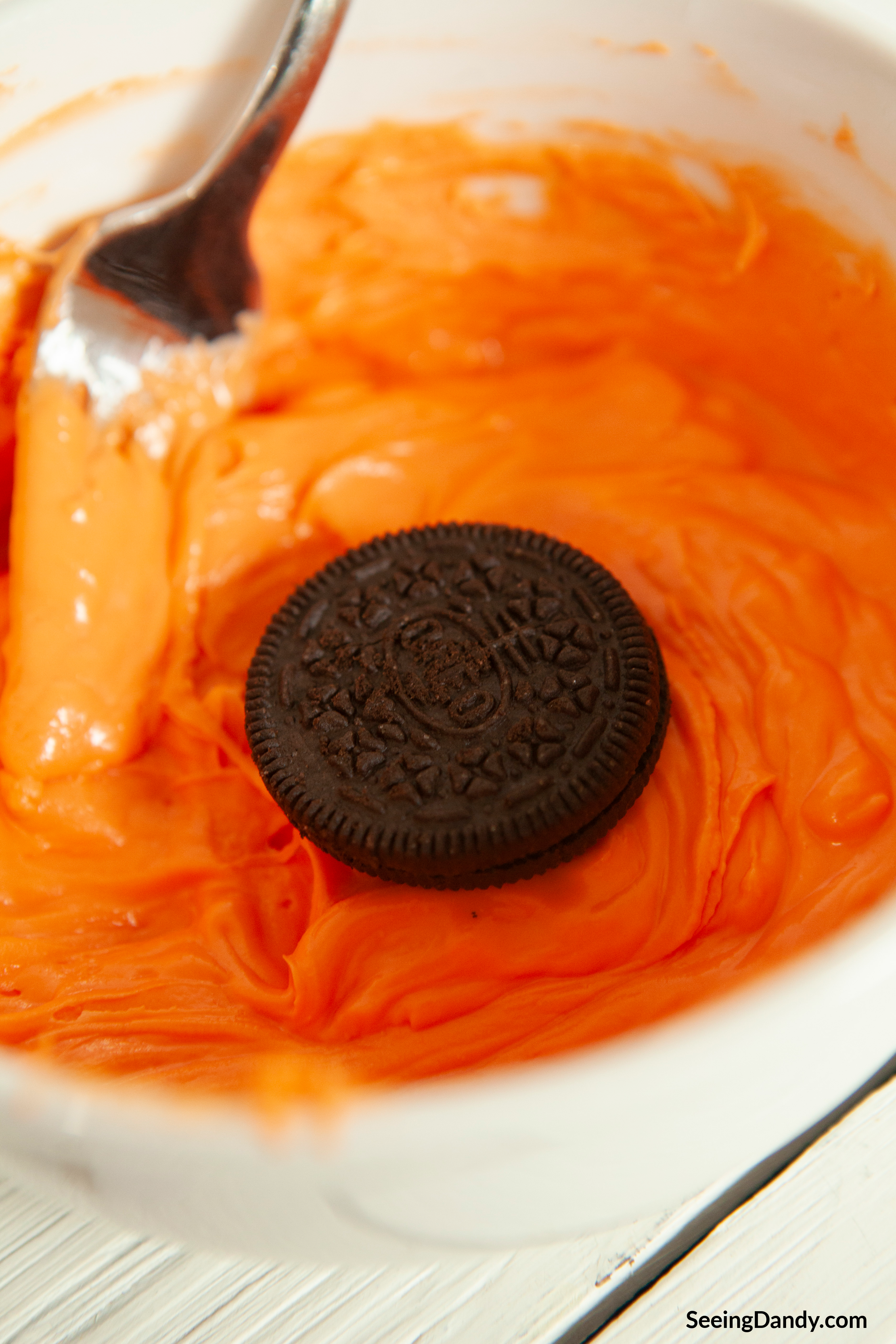 dipping oreo cookie in orange chocolate