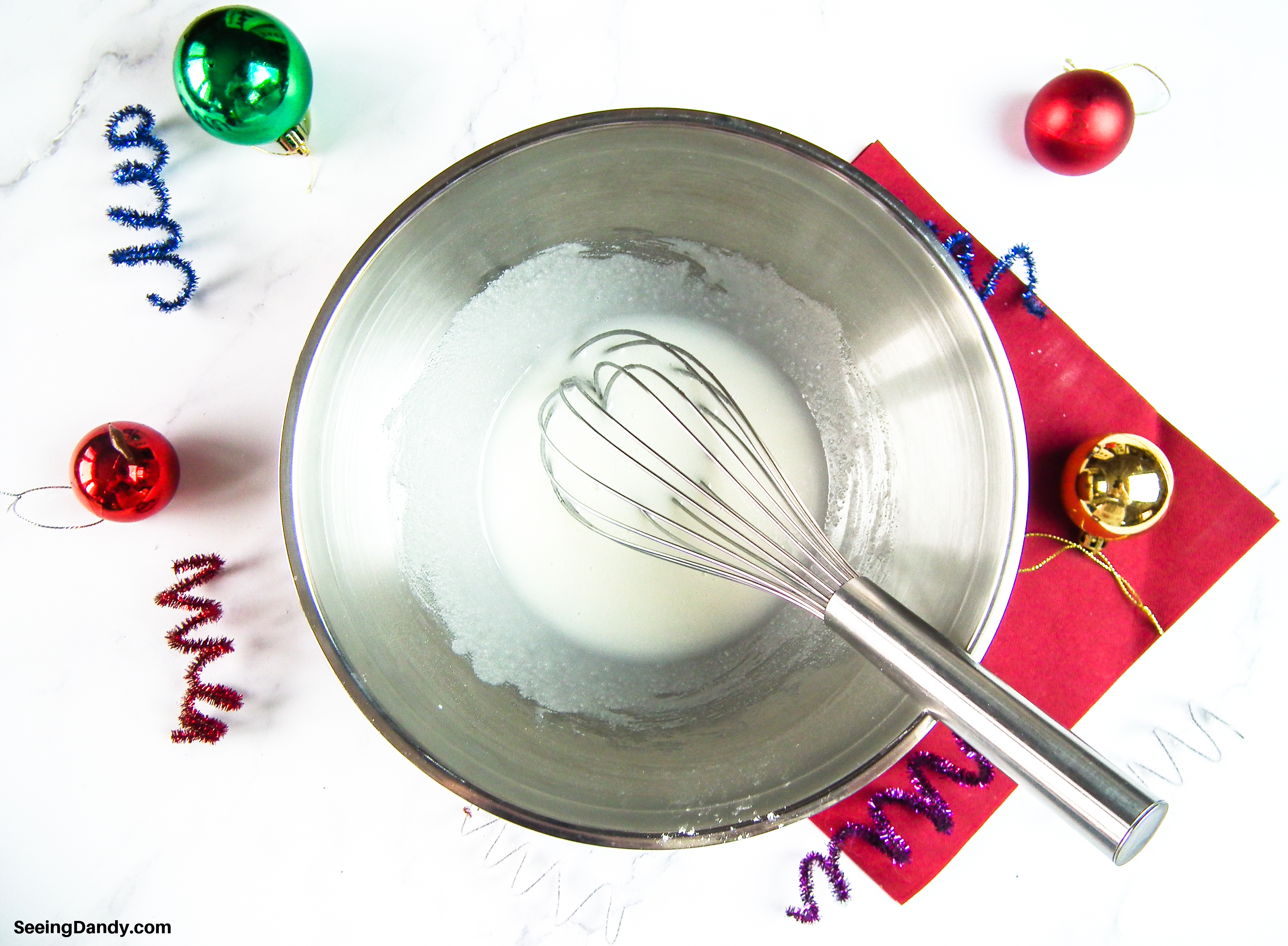 easy icing recipe, christmas ornaments, marble countertop, silver bowl, whisk