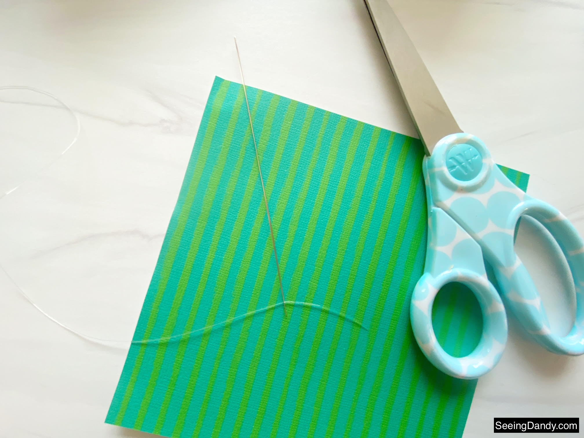 bracelet making bead needle, green blue stripe scrapbook paper, marble countertop, elasticity stretch bead cord, craft scissors, easy crafts, clear bracelet making elastic cord