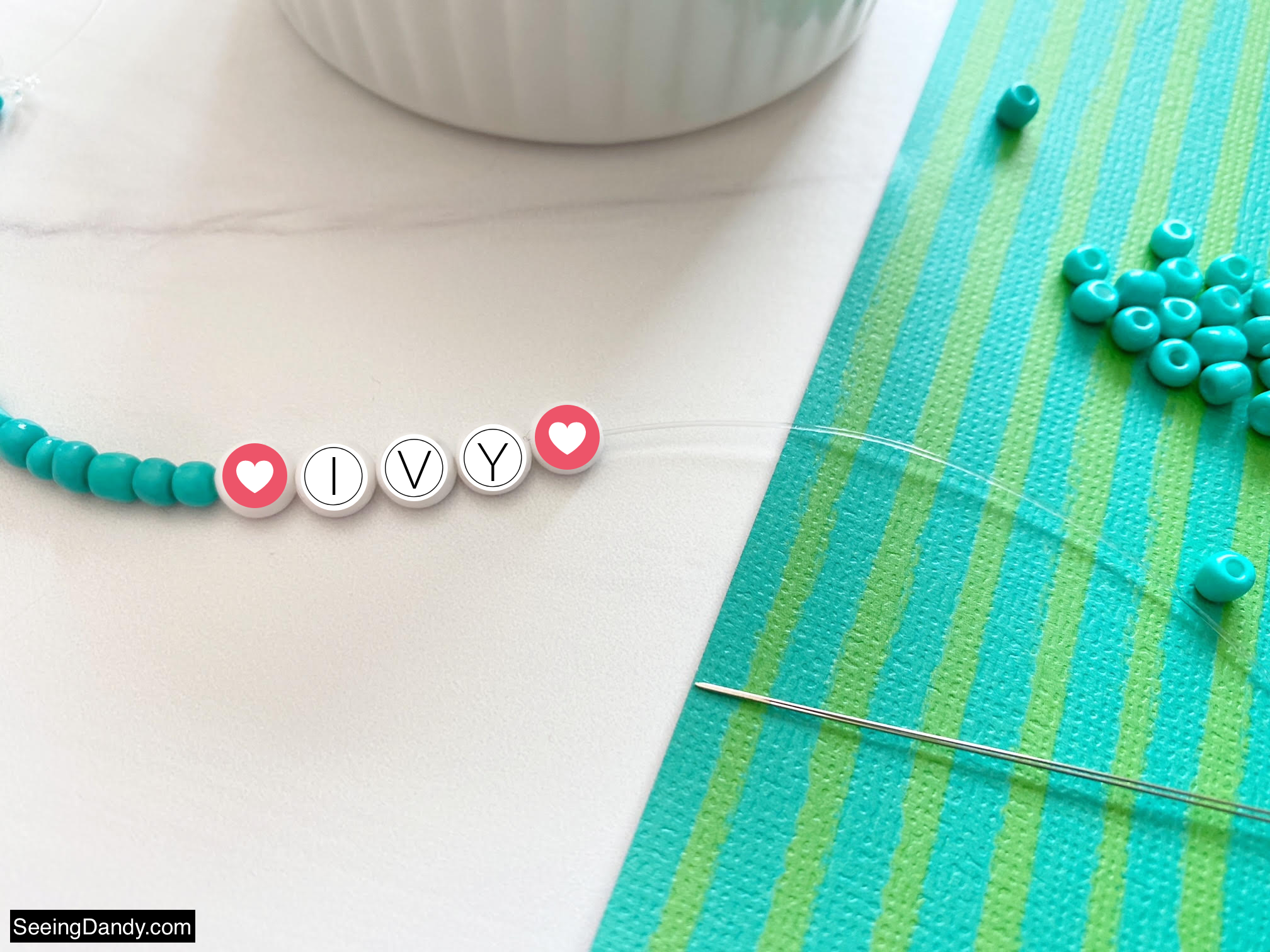 bracelet making bead needle, Beaded Alphabet Name Bracelets, beaded name bracelet, ivy name bracelet, heart letter beads, green blue stripe scrapbook paper, marble countertop, elasticity stretch bead cord, craft scissors, easy crafts, clear bracelet making elastic cord, turquoise glass seed beads, diy bracelet