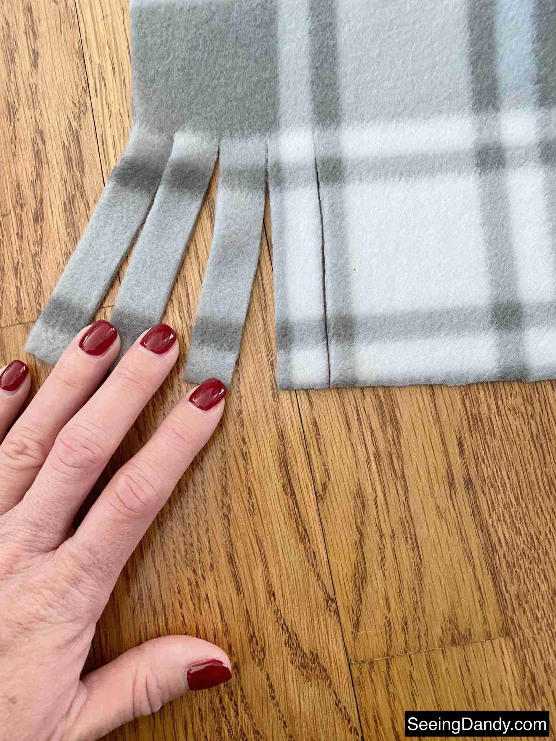 cutting scarf fringe, red purple gel nail polish, hardwood floor, plaid gray white fleece fabric