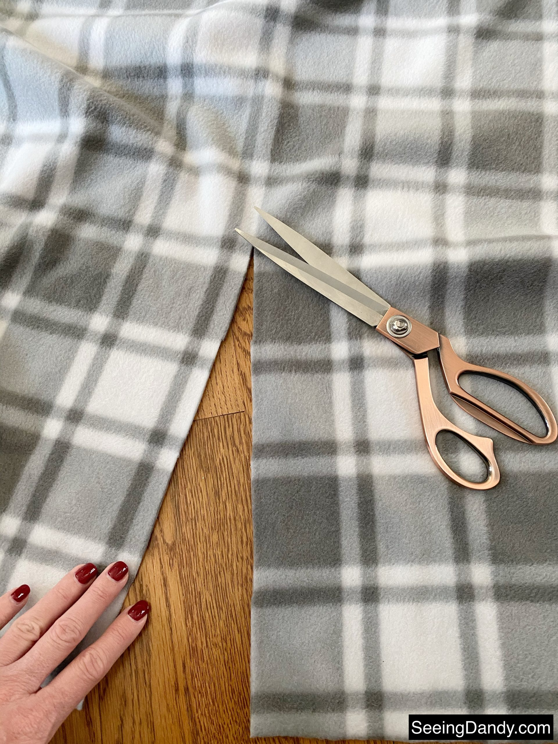 gray plaid cozy winter fabric, no sew, sewing project, holidaze rose gold scissors, hardwood floor, red gel nail polish