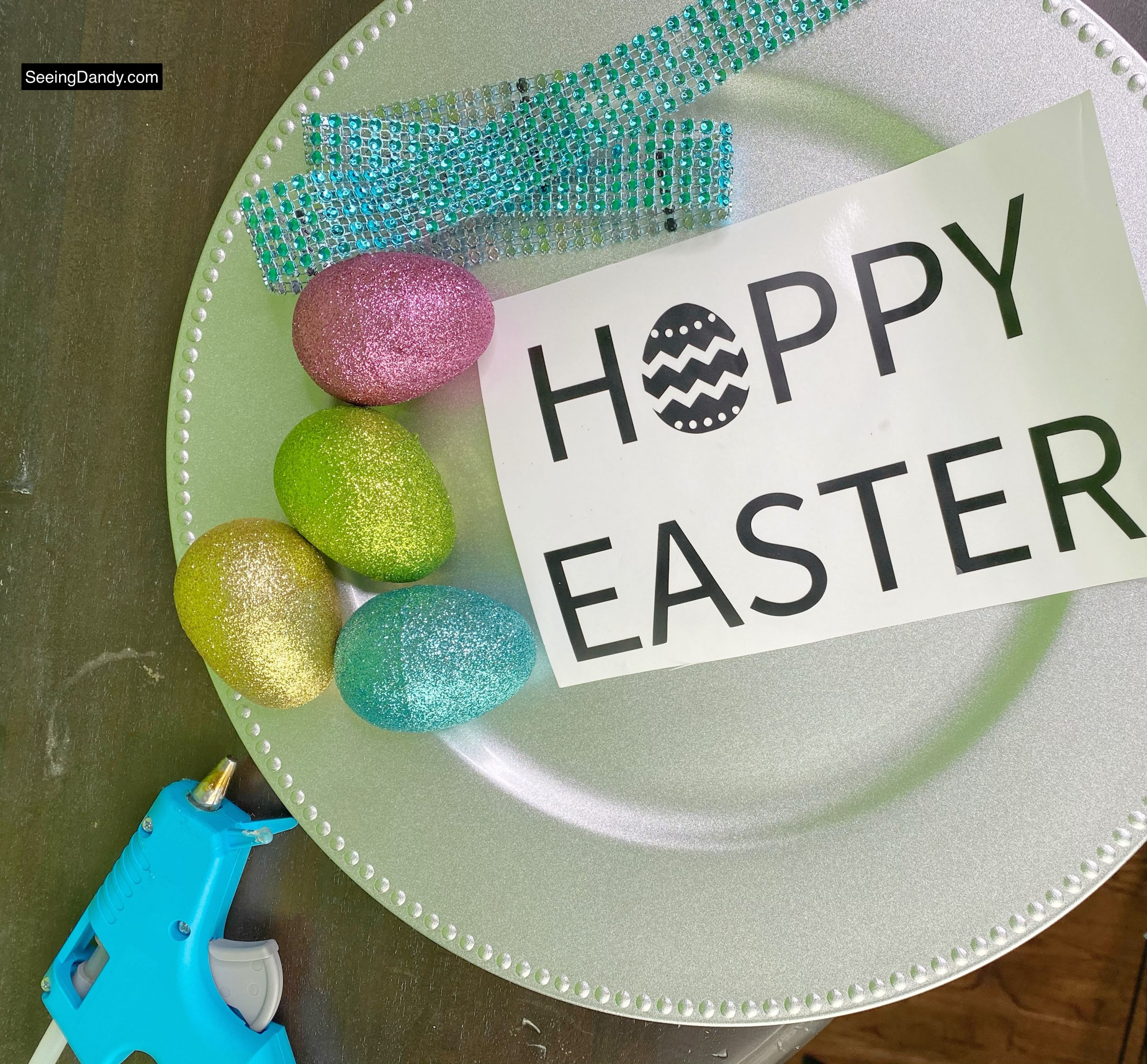 free svg file, dollar tree glitter easter eggs, happy easter svg file, hoppy easter svg file, vinyl craft idea, silver charger plate, dollar tree plastic charger plate, glue gun, teal jeweled ribbon