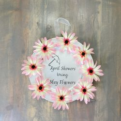 wreath ideas, silhouette craft, cricut craft, diy april showers bring may flowers sign, pink daisies, springtime decor, spring wreath craft, home decor, farmhouse style, dollar tree craft, silver plastic charger plate, farmhouse table, pink spring flowers