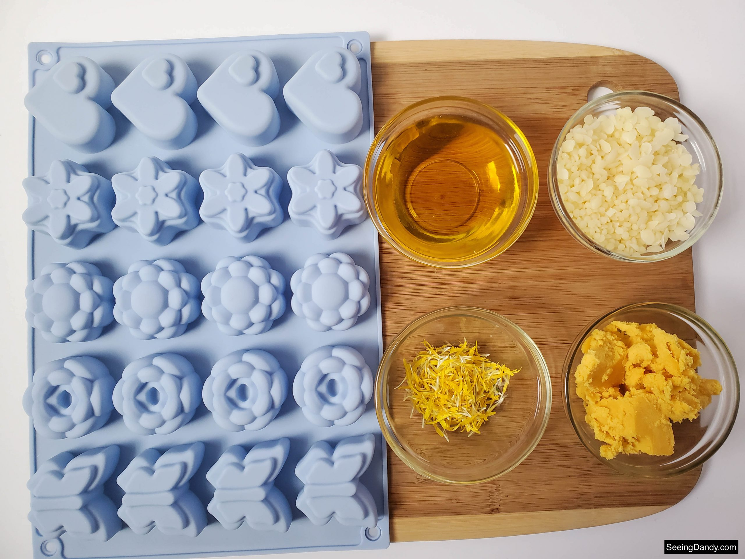 wood cutting board, glass mixing bowls, shea butter, beeswax, dandelion infused oil, fresh dandelion petals, silicone flower soap mold