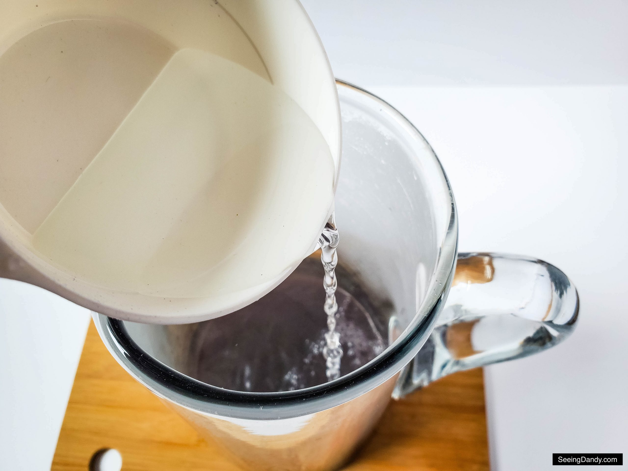 glass water pitcher, wood cutting board, pouring water