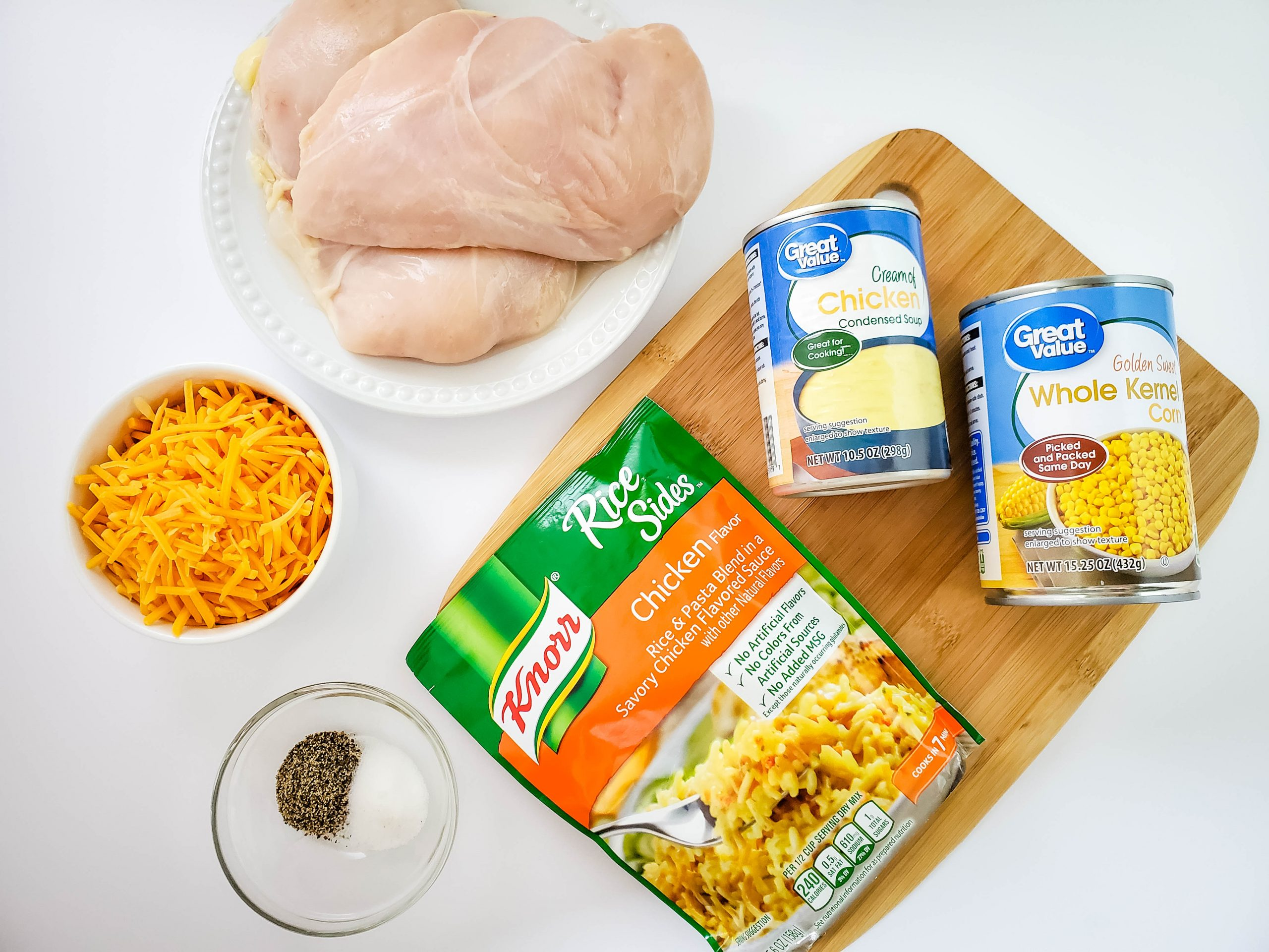 knorr chicken flavored rice, chicken breast, shredded cheddar cheese, great value cream of chicken soup, great value whole kernel corn, wooden cutting board